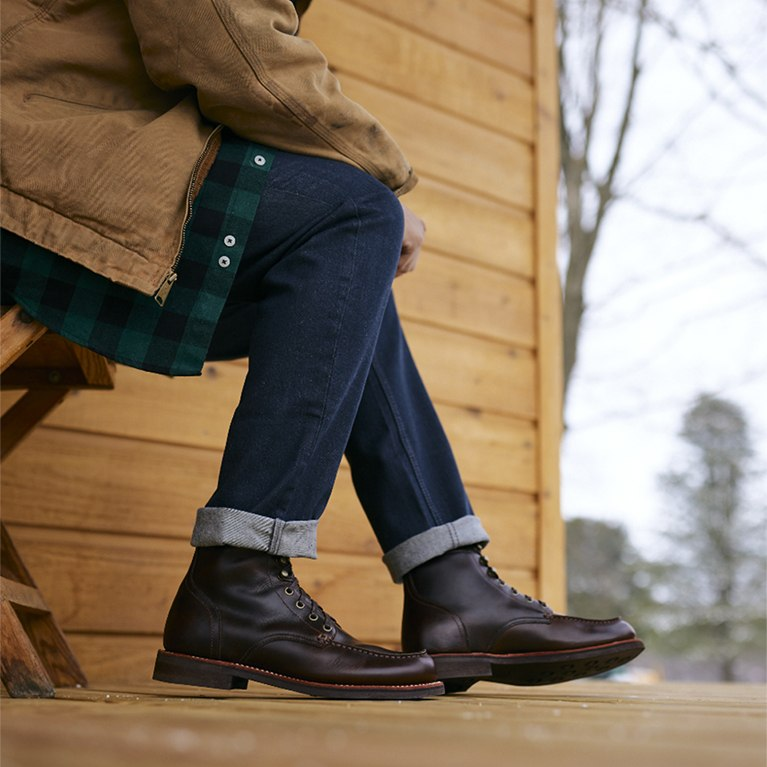 Men's leather boots on a wood deck